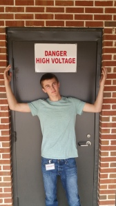 Wiles stands in front of a sign on a door that reads