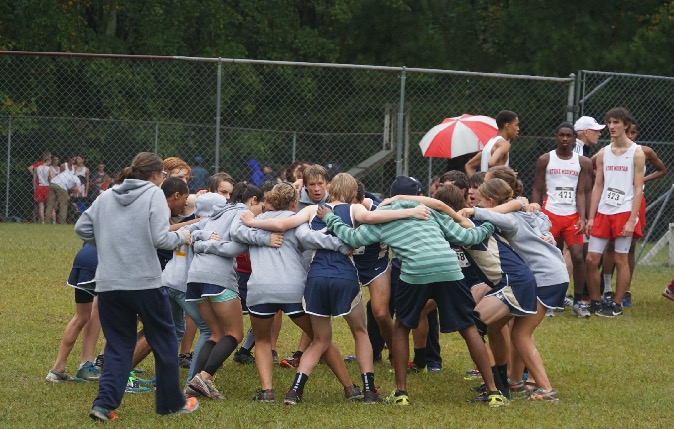 An excited teams helps gets the Varsity boys ready for their race by
