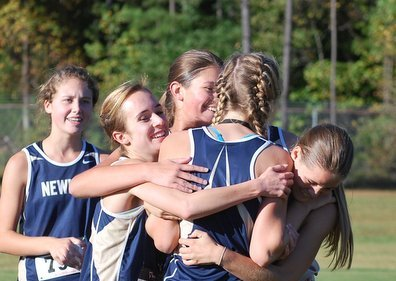 Varsity Girls celebrate after Hallman's victory and Caroline Thomas also placing in the Girl's Varsity race. (PHOTO, Freeman)
