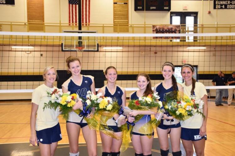Coach Wilson and Coach Kuehl stands with her four seniors on the court. Seniors with flowers from left to right, Jenni Young, Ansley Knight, Meg Oldham and Anna Brumby. (PHOTO courtesy of Knight)